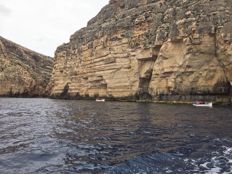 Verschillende bootjes met toeristen varen langs de rotswanden.